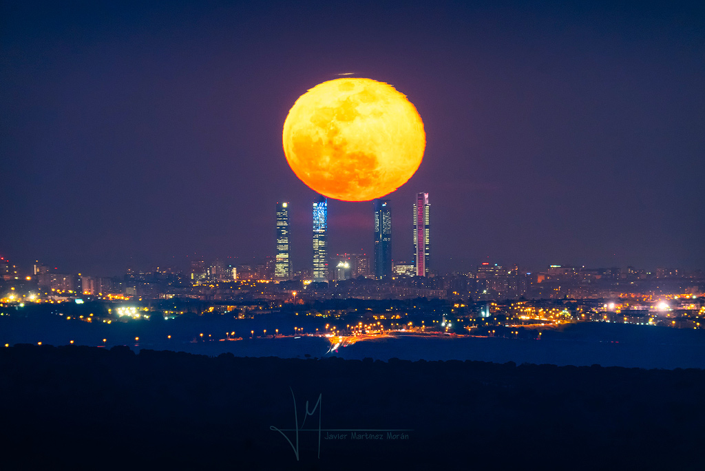 Quatre tours et la Lune de l\'équinoxe - La pleine lune se lève, le lendemain de l\'équinoxe, juste au-dessus des tours de la ville de Madrid, fortement déformée par la réfraction atmosphérique